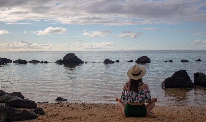 Finding a moment of peace while meditating to the sound of the gentle waves in Hawaii.